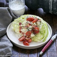Wedge salad on a round white plate with jar of blue cheese dressing