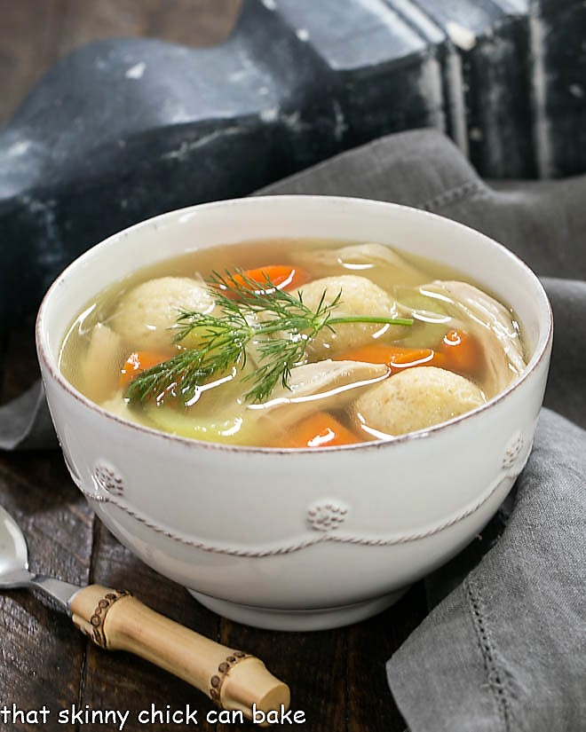 Chicken soup with vegetables topped with a sprig of dill and served with a bamboo spoon