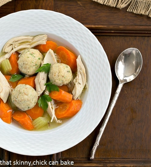 Overhead view of Chicken Soup with Matzo Balls AKA Jewish Penicillin in a white soup bowl with a spoon