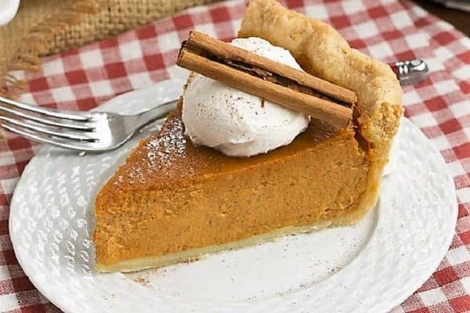 Classic pumpkin pie topped with whipped cream and a cinnamon stick