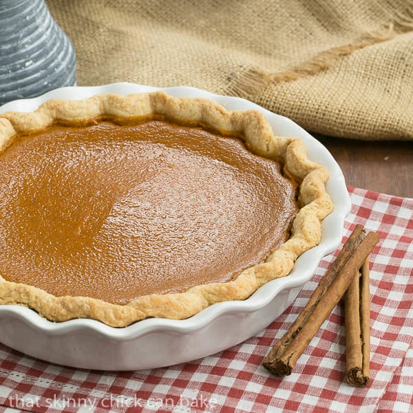 Classic Pumpkin Pie in a white ceramic pie plate on a red and white checked napin