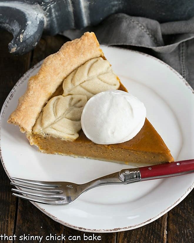 Overhead view of a Pumpkin Pie slice garnished with whipped cream