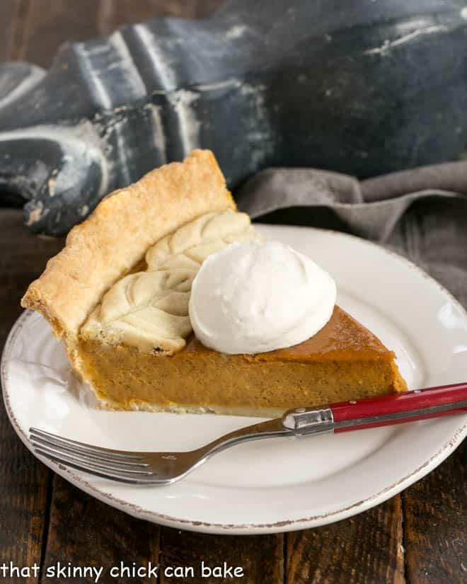 Slice of pumpkin pie on a white dessert plate