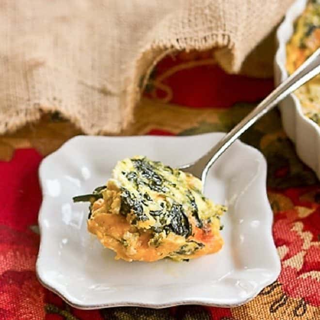 A spoonful of Cheesy Spinach Souffle on a small white plate