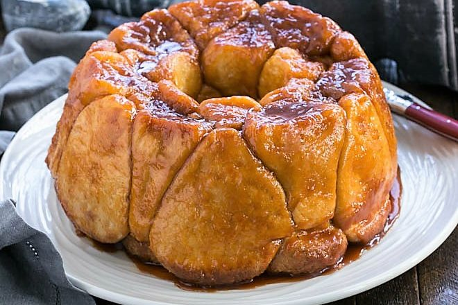 Easy Monkey Bread on a white serving plate with a red handle knife