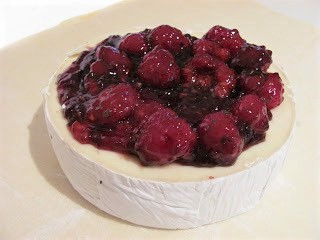 Brie with berry topping on a sheet of parchment
