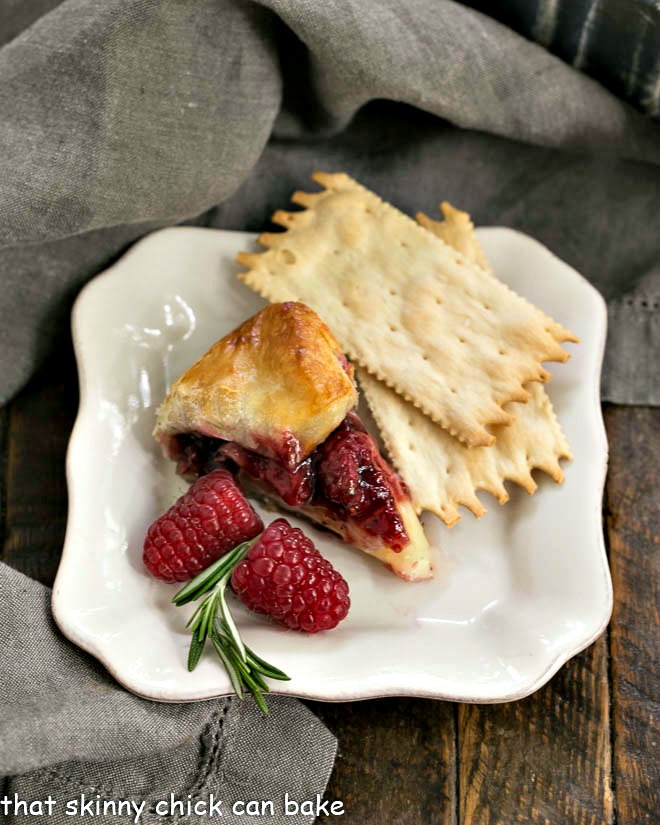 Slice of raspberry brie en croute on an appetizer plate with crackers and fresh raspberries