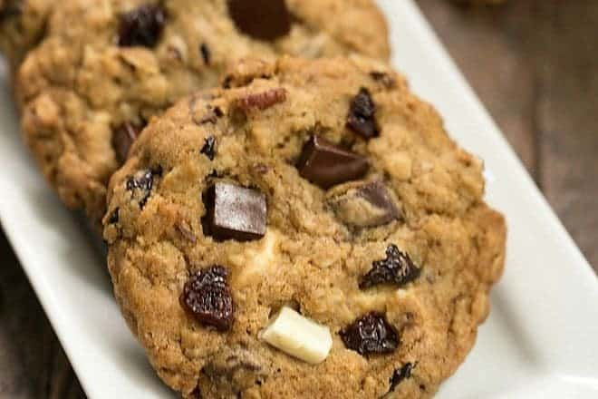 Oatmeal Cookies with Chocolate Chunks, Pecans, and Dried Cherries on a white tray with pecans and cherries