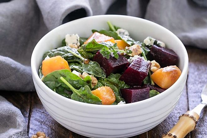 Beet salad in a small white bowl with a bamboo handle fork