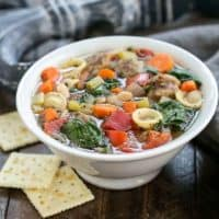 Italian Sausage and Pasta Soup in a white bowl with saltine crackers