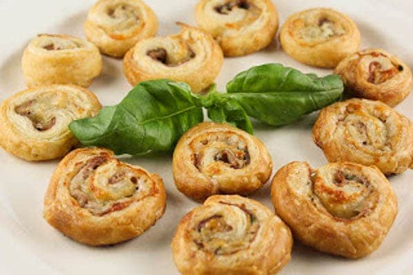 Prosciutto Gruyère Pinwheels on a white tray with a sprig of basil