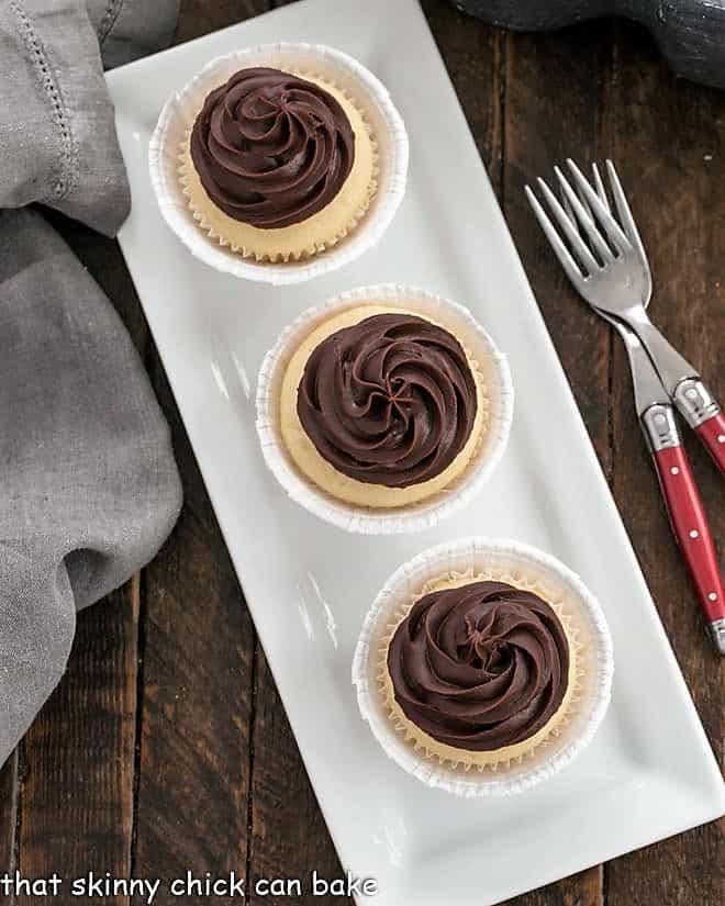 Overhead view of 3 Boston Cream Pie Cupcakes on a narrow white platter