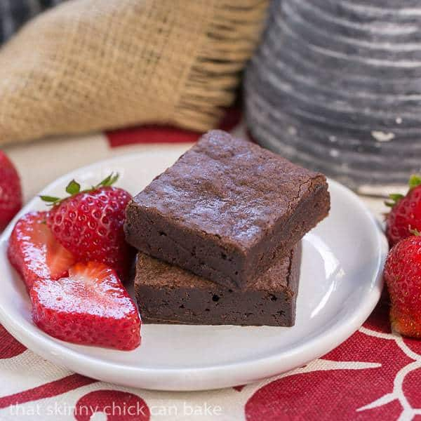 Cocoa Brownies with Browned Butter stacked on a white plate with strawberry slices