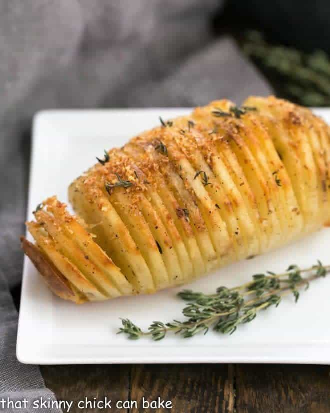 Hasselback Potatoes on a square white plate with a sprig of thyme