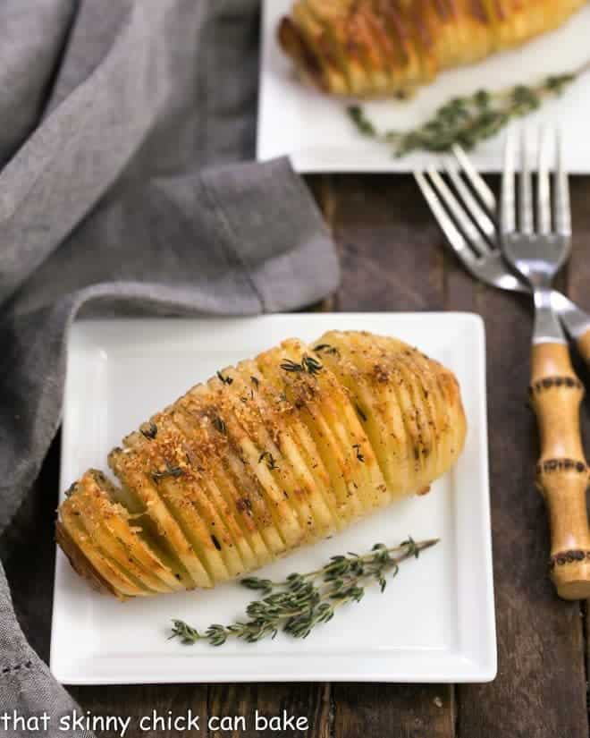 Hasselback Potatoes on square white ceramic plates with bamboo forks