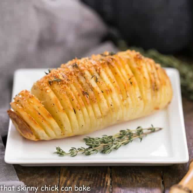Hasselback Potatoes on a white plate with thyme garnishes