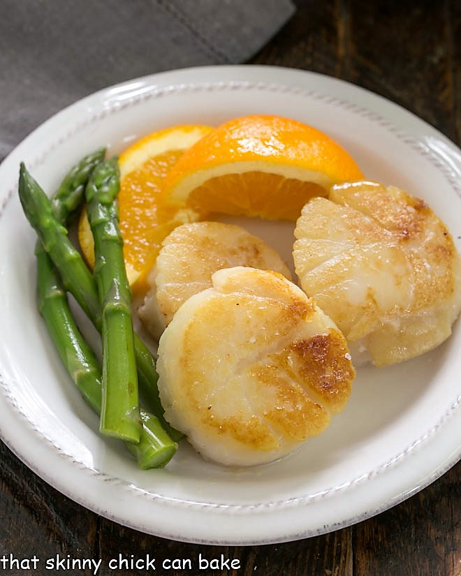 Scallops, asparagus and orange wedge on a white ceramic plate