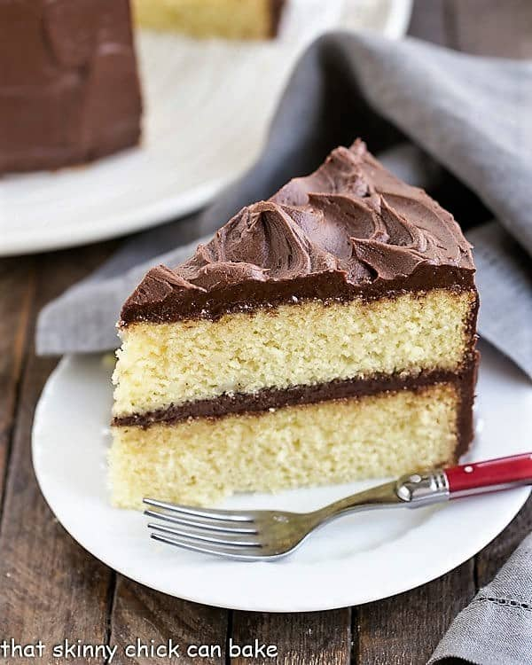 Slice of Perfect Yellow Cake Recipe with Chocolate Buttercream on a white cake with a red handled fork