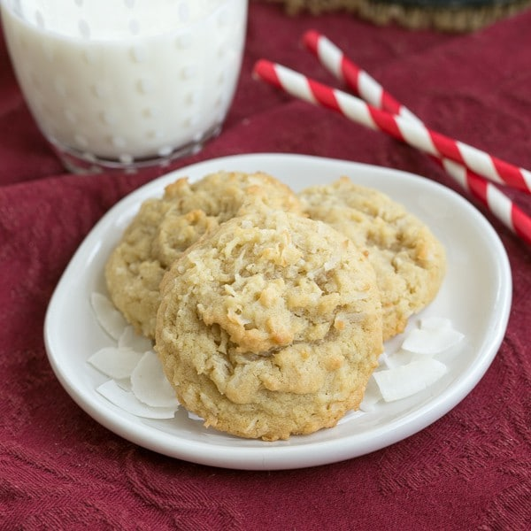 Chewy Coconut Cookies on a white plate with a glass of milk and straws