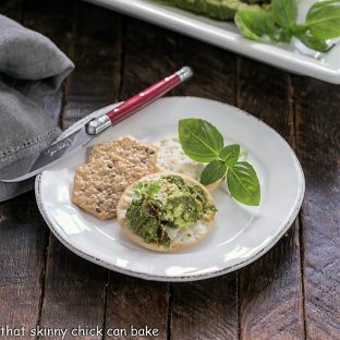 Pesto dip with crakers on a round white appetizer plate