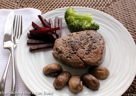 Pepper Steak on a white plate with mushrooms, beets and broccoli