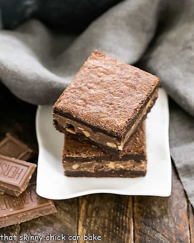 Two Symphony Toffee Brownies stacked on a square white dish