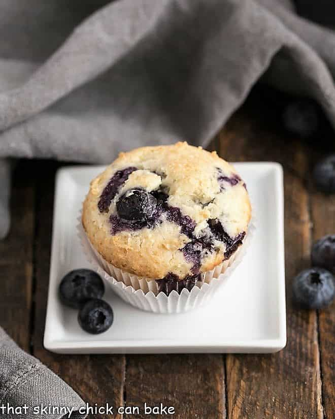 Blueberry Sour Cream Muffins on a white square plate with fresh blueberries