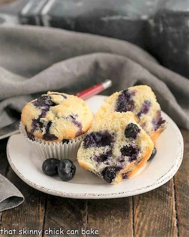 Blueberry Sour Cream Muffins on a round white plate with one cut to show the interior