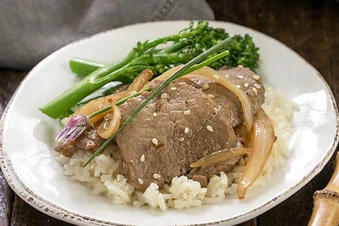 Pork bulgoi on a round white plate over rice with broccolini