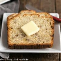 Buttermilk Banana Bread on a square white plate with a red handled knife