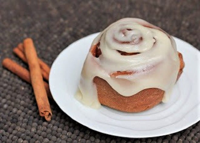 Frosted Cinnamon Roll on a white plate