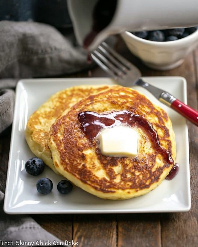 Buttermilk Pancakes with Blueberry Syrup on a plate topped with butter and syrup