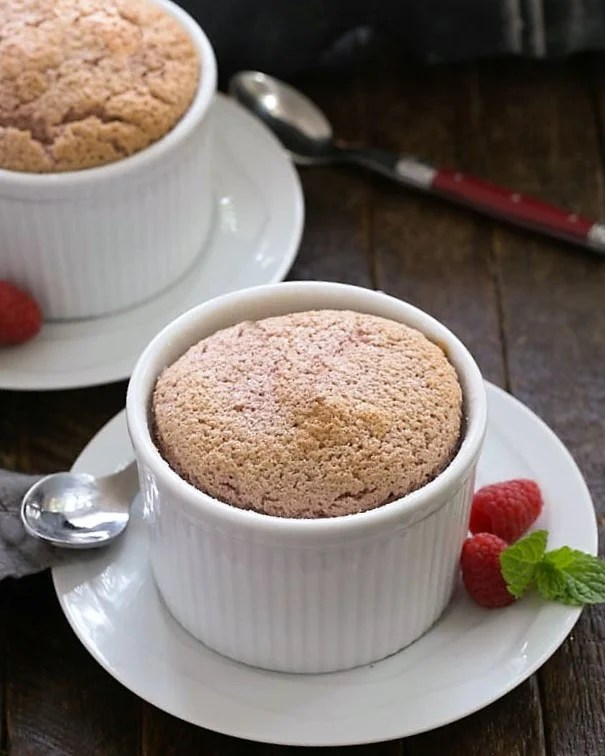 Two raspberry souffles on white dishes with spoons