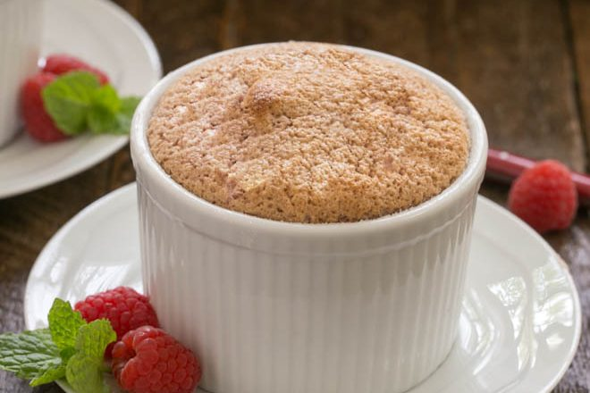A raspberry souffle on a white plate with mint and raspberries to garnish