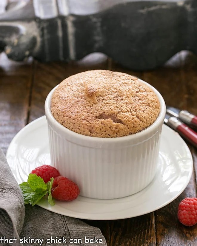 Individual Raspberry Souffle on a white plate with a raspberry garnish