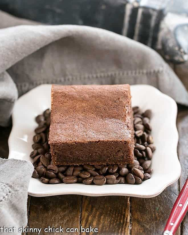 Kahlua Brownies on a bed of coffee beans on a square white plate