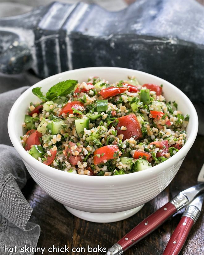A taboouli recipe in a white serving bowl with 2 forks
