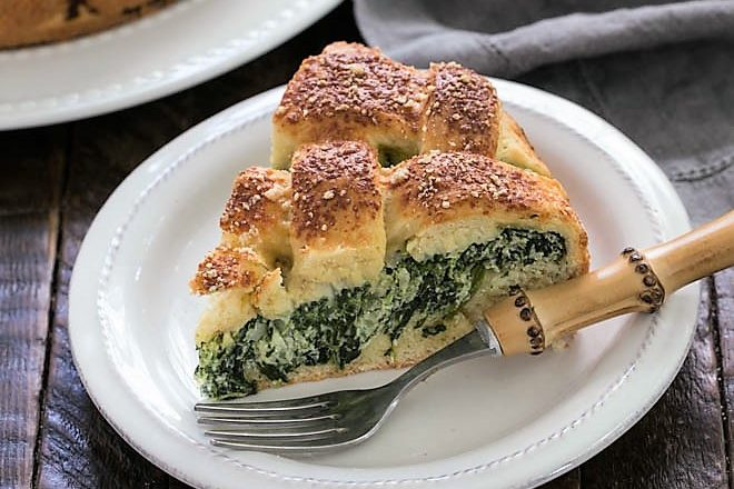 Slice of spinach torta rustica on a small white plate with a bamboo handled fork