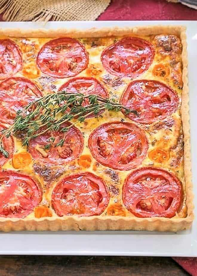 Tomato Gruyere Tart on a white tray topped with a sprig of thyme
