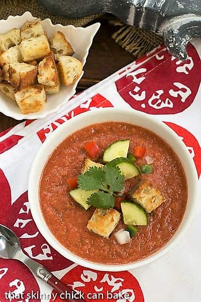 Overhead view of Classic Gazpacho with Homemade Croutons in a white bowl topped with cucumbers, peppers and croutons