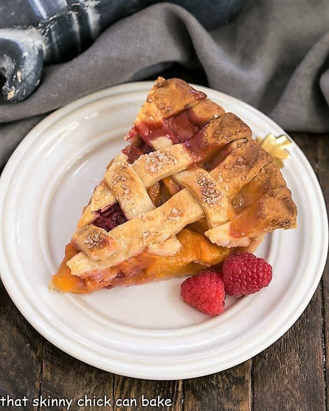 Overhead view of Peach pie recipe with raspberries slice on a white dessert plate