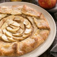 Rustic Apple Tart on a white plate with apples in the background