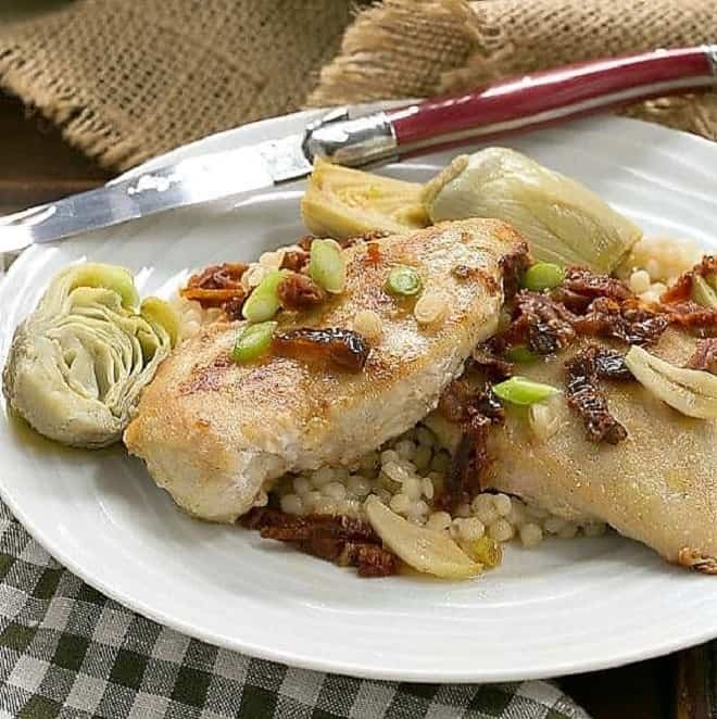 Chicken with Artichokes over Israeli Couscous on a white dinner plate
