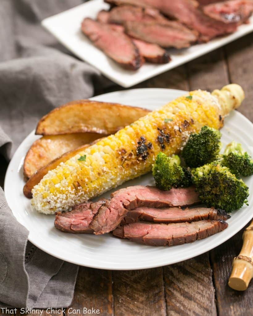 Marinated Grilled Ginger Flank Steak on a white plate with corn on the cob, broccoli and potato wedges