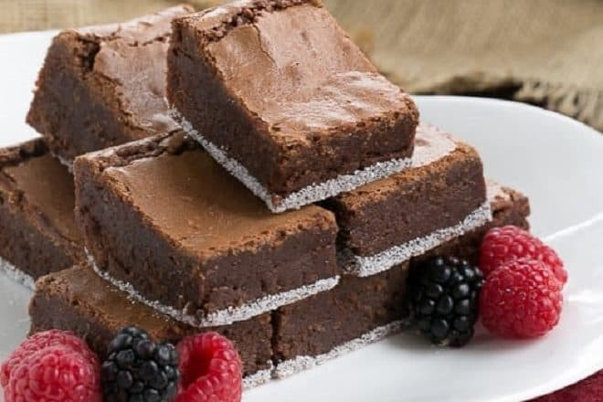 One Bowl Fudgy Brownies on a white serving tray with a berry garnish