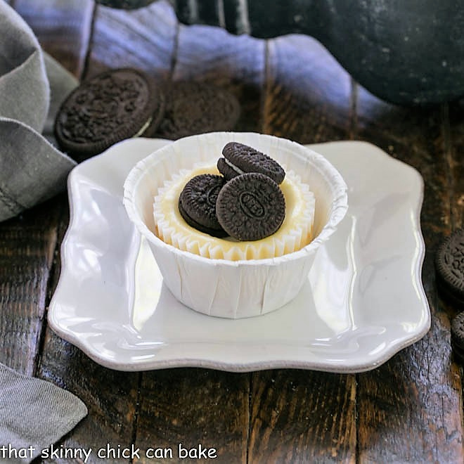 A mini Oreo cheesecake on a square white plate