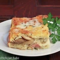 Slice of Monte Cristo Bread pudding on a round white plate garnished with parsley
