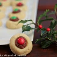 A holiday thumbprint cookie perched on a cookie tray with a sprig of holly