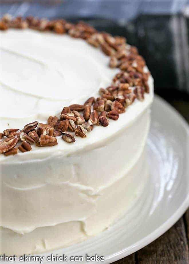 Partial view of whole cheesecake stuffed carrot cake with cream cheese frosting
