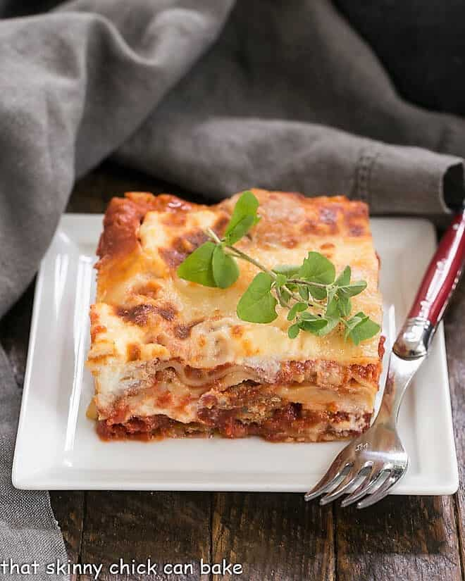 Lasagna with Italian Sausage on a white plate with a red handled fork